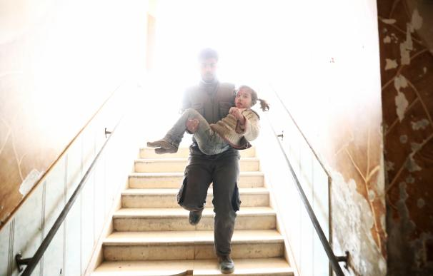 Un voluntario lleva a una niña herida tras un bombardeo gubernamental en la zona rebelde de Douma, cerca de Damasco, el 25 de febrero de 2017 (AFP PHOTO / Abd Doumany)