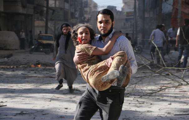 Un hombre huye de los barriles de explosivos con una niña en brazos
