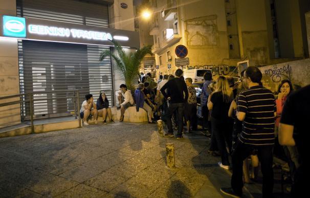 Varios ciudadanos griegos hacen cola delante de un cajero por la noche