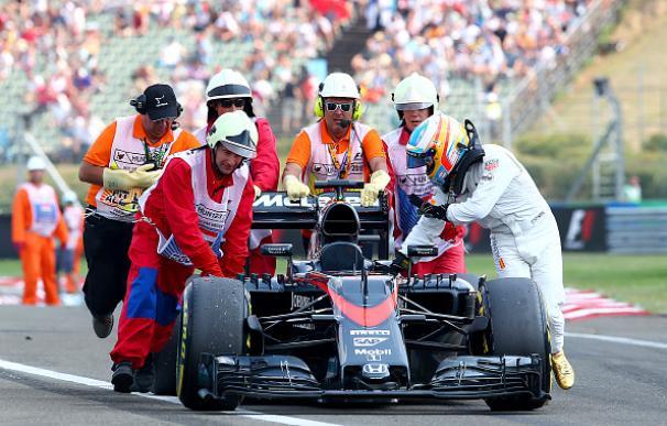 Alonso llega al garaje empujando el McLaren
