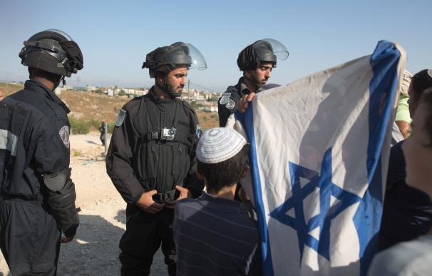 Jewish settlers, holding an Israeli flag, are bloc