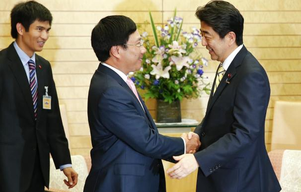 Japan's Prime Minister Shinzo Abe (R) shakes hands