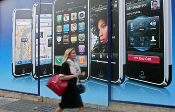 Una mujer pasea por delante de un cártel de iPhone