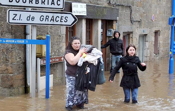 Unas personas se ven obligadas a abandonar sus casas por las inundaciones en la localidad de Guincamp, en Francia - EFE