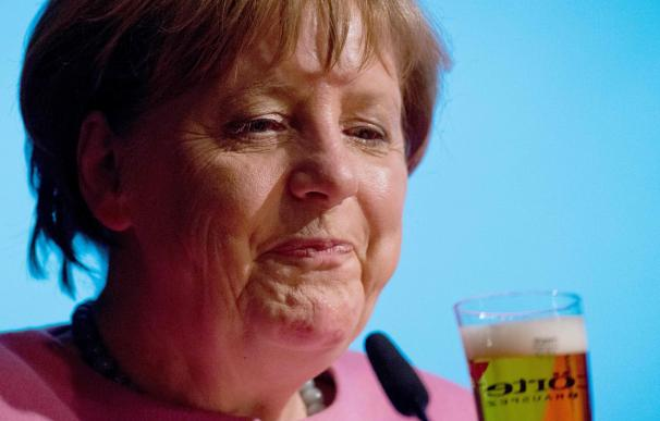 German Chancellor Angela Merkel drinks a beer at a