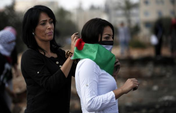 A Palestinian woman is helped to put a Hamas scarf