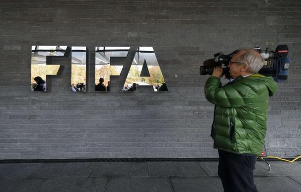 A cameraman films the FIFA sign at the football's