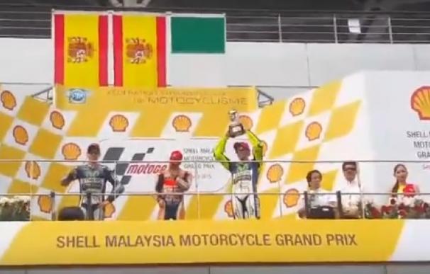 Lorenzo, con el pulgar hacia abajo mientras Rossi levanta el trofeo.