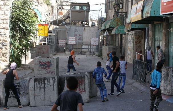 Palestinian protesters throw stones towards Israel