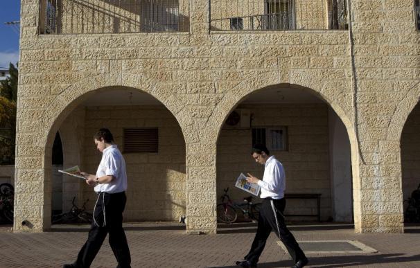 Unos judíos ultraortodoxos leen el periódico mientras caminan por la colonia judía de Ramat Shlomo