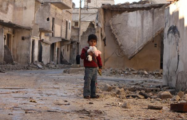 Un niño en Alepo, junto a los escombros con un peluche