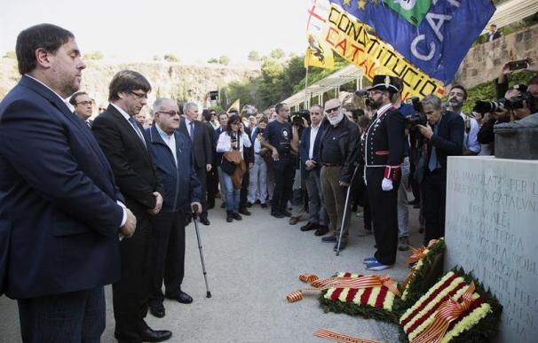 El presidente de la Generalitat, Carles Puigdemont (2i), junto al vicepresidente Oriol Junqueras (i), durante la tradicional ofrenda ante la tumba del presidente de la Generalitat republicana Lluís Companys