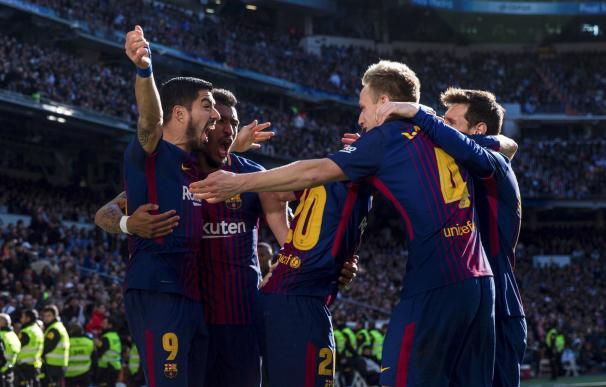 El jugador uruguayo del FC Barcelona, Luis Suárez (i), celebra con sus compañeros tras marcar el primer gol del partido correspondiente a la jornada 17 de Liga en Primera División que el Real Madrid y el FC Barcelona, disputaron hoy en el estadio Santiago