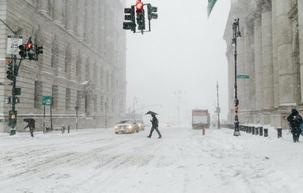 Peatones caminan bajo la nieve