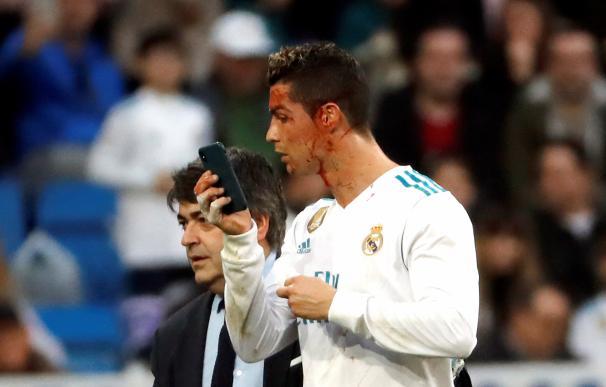 El delantero portugués del Real Madrid, Cristiano Ronaldo, se mira en un teléfono móvil tras ser golpeado en la cara durante el partido de la vigésima jornada de Liga que disputan esta tarde ante el Deportivo en el estadio Santiago Bernabéu de Madrid. EFE