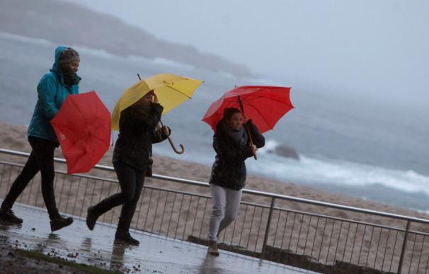 Tres mujeres se protegen de la lluvia en el paseo marítimo de A Coruña (EFE/Cabalar)
