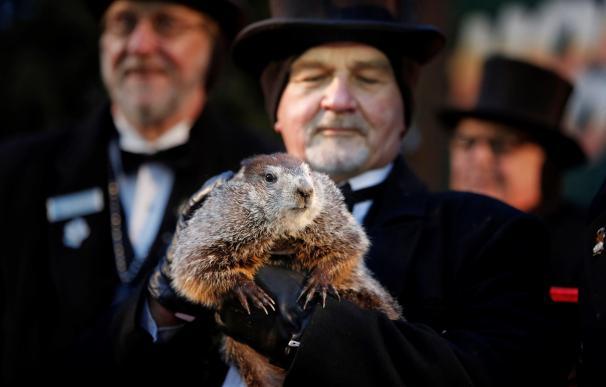 El cuidador John Grifiths (d), sostiene a la marmota Phil mientras se lee la predicción en Punxsutawney, Pensilvania (EFE/ David Maxwell)