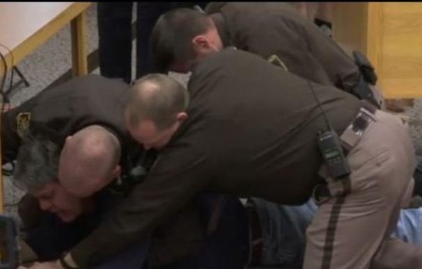Captura de vídeo del momento en el que el padre de las víctimas es retenido por los agentes