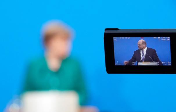 Angela Merkel y Martin Schulz (en pantalla) en una rueda de prensa