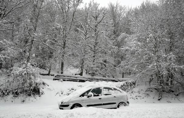 Un coche permanece atascado en la nieve en el Alto de Mezquiriz, Navarra