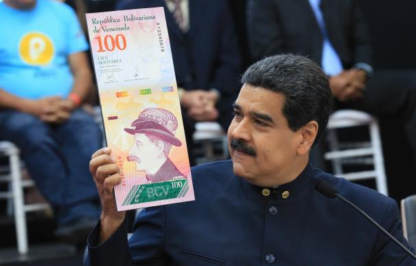 Nicolás Maduro muestra una imagen de un billete de 100 bolívares en una rueda de prensa