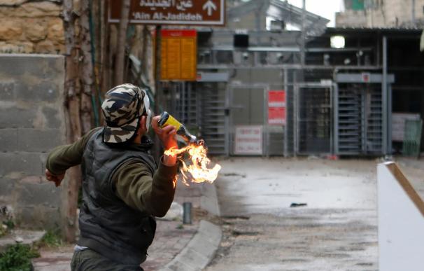 Un palestino lanza un cóctel molotov contra soldados israelíes durante enfrentamientos en Hebron, Palestina, hoy, 30 de marzo de 2018. EFE/ Abed Al Hashlamoun