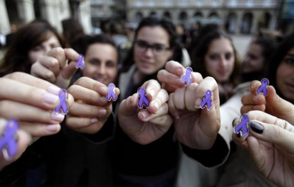 Varias jóvenes muestran lazos de color violeta, que simbolizan la lucha contra la violencia machista. (EFE)