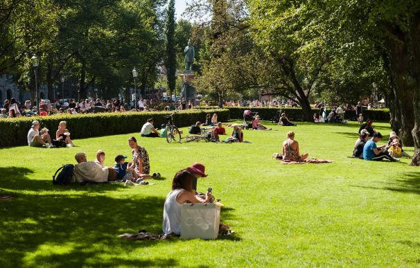 Finlandeses disfrutan del sol en un parque de Helsinki.