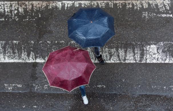 En la imagen, dos peatones cruzan por un paso de cebra, tapándose de la lluvia con su paraguas, en la ciudad gallega de Ourense. EFE/Brais Lorenzo