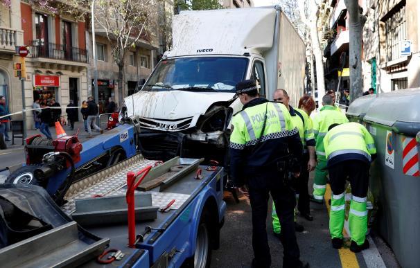 Agentes de la Guardia Urbana de Barcelona retiran el camión