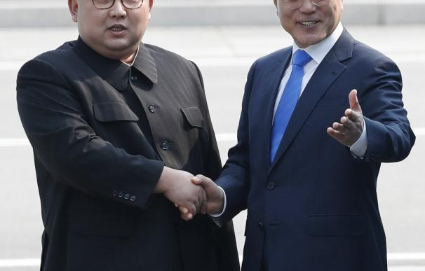 Moon Jae-in (d) y Kim Jong-un (i) se dan la mano en la línea de demarcación militar (MDL)