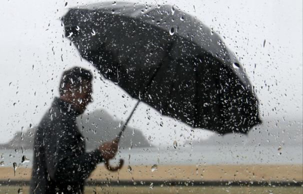 Un hombre se protege de la lluvia con una paraguas mientras pasea junto a la bahía de La Concha de San Sebastián. (Juan Herrero / EFE)