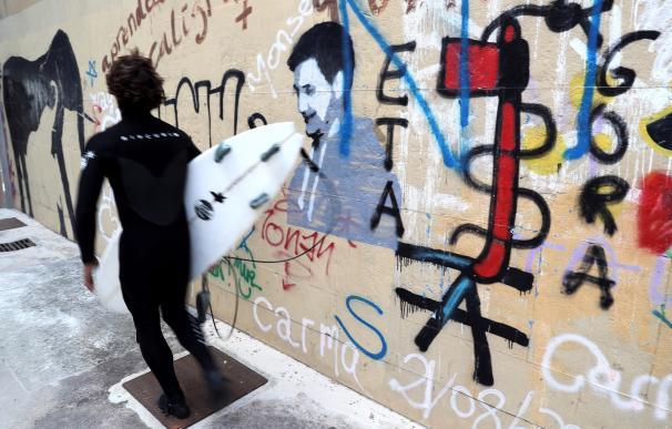 Un surfista pasa junto a una pintada a favor de la banda terrorista ETA en el barrio de Gros de San Sebastian. EFE/Juan Herrero