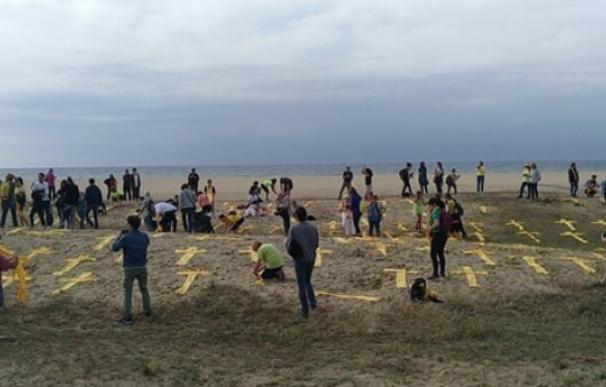 Los CDR colocan cruces amarillas con toallas en la playa de Mataró