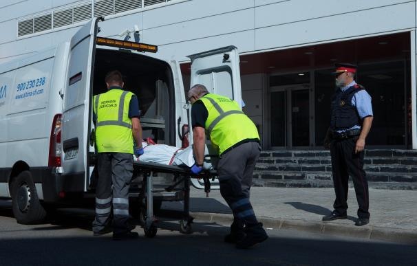 Miembros del servicio judicial retiran el cadáver.
