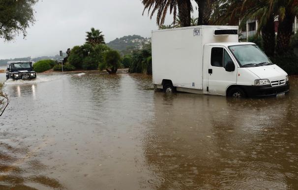 Un vehículo circula por una calle anegada en Alicante