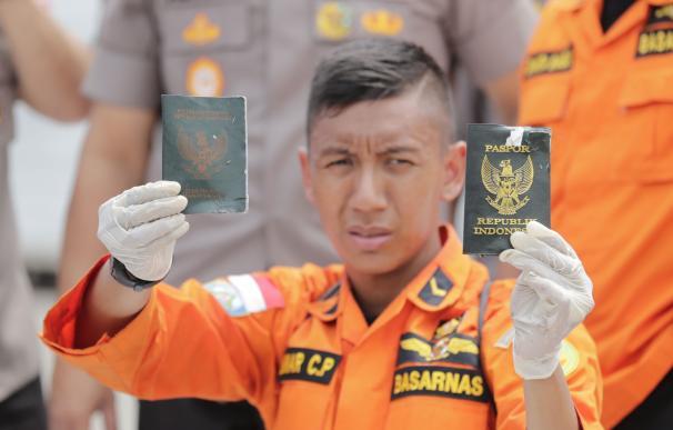 Un rescatista muestra los pasaportes de dos pasajeros del accidente aéreo de este lunes en el puerto de Tanjung Priok