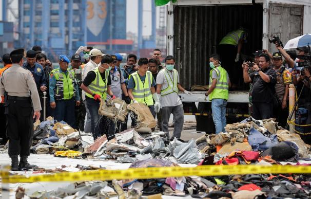 Miembros de los servicios de rescate recuperan restos del avión siniestrado en el mar de Java.