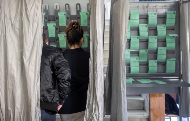 Una pareja escoge la papeleta en el colegio electoral ubicado en la biblioteca de Sanlúcar de Barrameda (Cádiz). EFE/Jose Manuel Vidal.