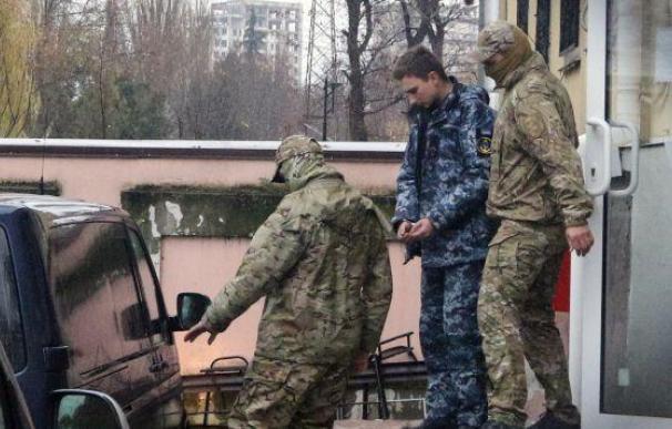 Miembros de los Servicios de Seguridad de Rusia escoltan a un marinero ucraniano detenido desde el tribunal de Simferópol, en Crimea. (Foto: EFE)