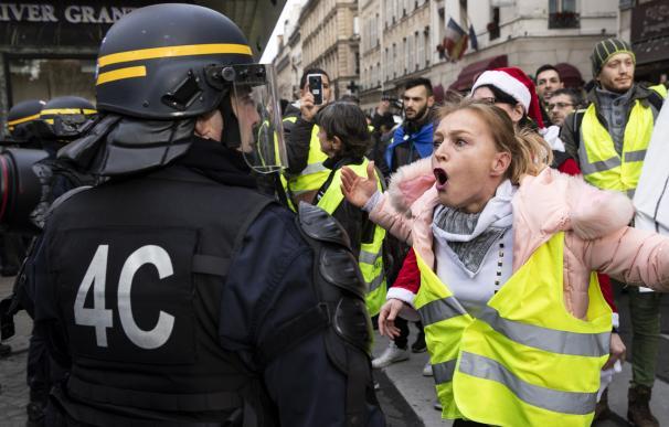 Una manifestante grita a la policía antidisturbios durante la protesta de 'Chalecos Amarillos' cerca de La Madeleine en París, Francia, el 22 de diciembre de 2018 (EFE/EPA/ETIENNE LAURENT)
