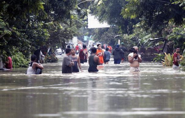 Numerosos filipinos atraviesan una calle inundada en Bulan