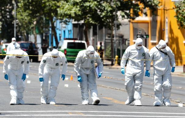 Miembros de la Policía de Investigaciones (PDI) de Chile revisan la zona donde se produjo hoy una explosión en el centro de Santiago (EFE).