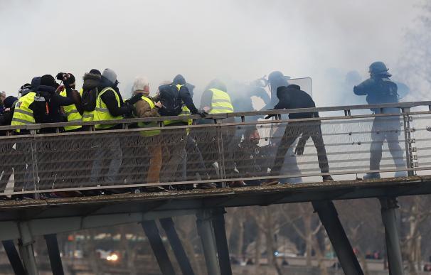 La policía antidisturbios se enfrenta a los manifestantes cuando intentan cruzar el río Sena durante la protesta de 'chalecos Amarillos' en París, el 5 de enero de 2019. (EFE/EPA/IAN LANGSDON)