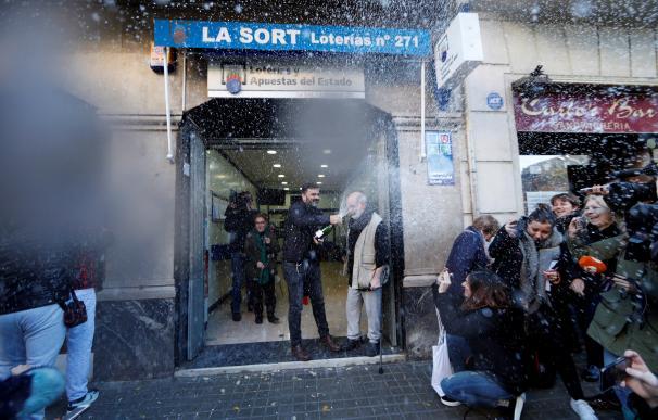 El dueño de la administración de lotería de la calle Travessera de Gràcia muestra su alegría tras haber vendido integramente el primer premio del sorteo de El Niño (EFE/Alejandro García)