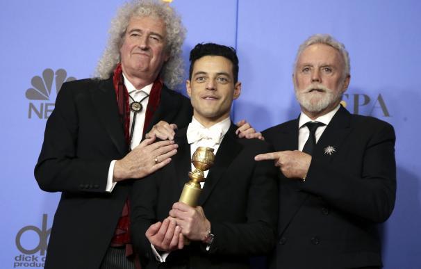 Los miembros de Queen, Roger Taylor y Brian May, posan con el galardonado Rami Malek