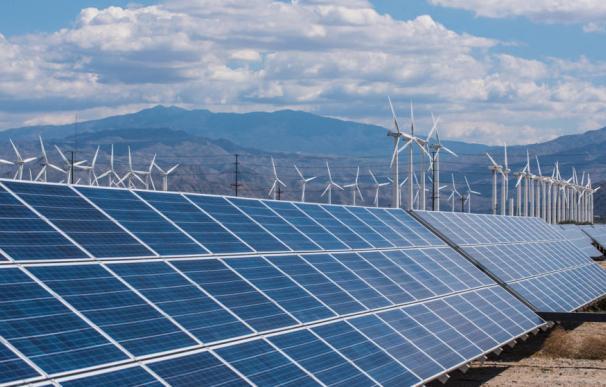 Instalación de paneles solares junto a un parque eólico.