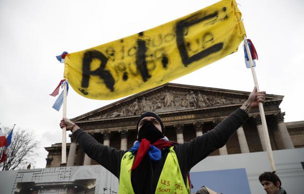 Un manifestante de los 'chalecos amarillos' sostiene una pancarta que reza 'RIC' (Referéndum de Iniciativa Ciudadana) EFE