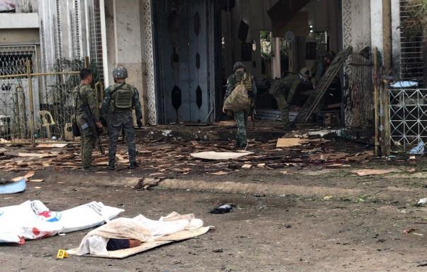 Soldados filipinos reúnen evidencias junto a los cuerpos cubiertos de víctimas frente a una iglesia tras las explosiones en la ciudad de Jolo, Sulu, Filipinas, el 27 de enero. (EFE/EPA/PEEWEE BACUNO)