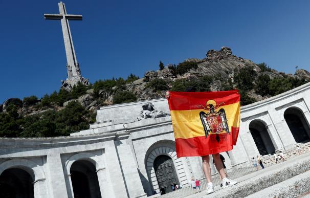 Una persona despliega una bandera anticonstitucional en la esplanada del Valle de los Caídos.